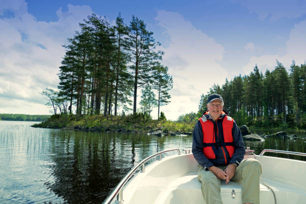 Smiling 73 years old senior wearing  a cap and a life jacket sitting in front of a motorboat sailing in Gastrikland,Sweden stock photo