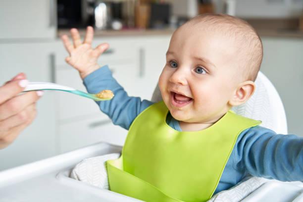 lächelnd 8 monate alte baby junge zu hause in hochstuhl fed solide nahrung von mutter mit löffel - füttern stock-fotos und bilder