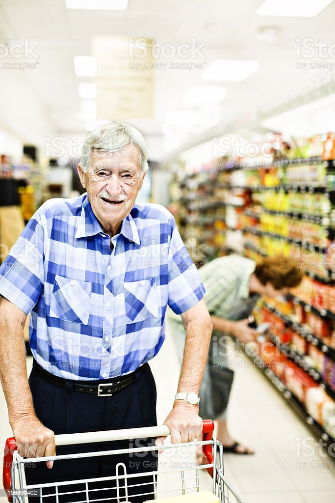 Smiling 87 year old man pushes cart in supermarket stock photo