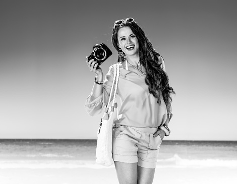 smiling active woman on seacoast showing digital SLR camera