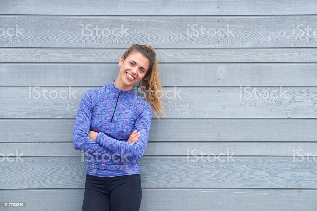 Smiling active woman standing with arms crossed photo libre de droits
