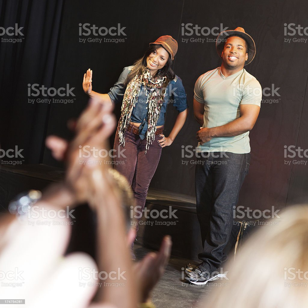 Smiling actors bowing on stage after performance stock photo