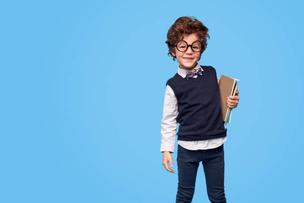 Smiling adorable wunderkind with notebooks Happy little boy in glasses holding notepads smiling at camera while standing against blue background child prodigy stock pictures, royalty-free photos & images