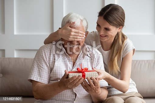 Smiling adult daughter closing older father eyes, preparing surprise, holding gift box with red bow in hand, young woman congratulating dad with birthday or fathers day, sitting on couch at home