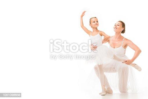 466300721 istock photo smiling adult female coach helping little ballerina exercising isolated on white background 1051098856