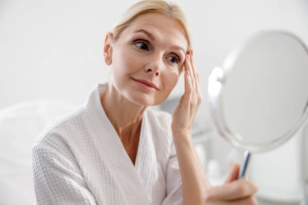 Smiling adult lady looking at herself in mirror stock photo