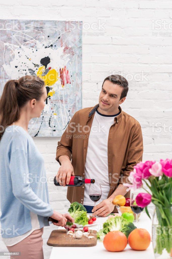 sorrindo vinho derramando do homem adulto no vidro para esposa enquanto ela cozinha - foto de acervo
