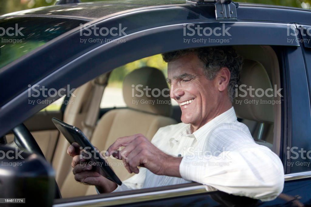 Smiling Adult Man Using DIgital Tablet in Car royalty-free stock photo