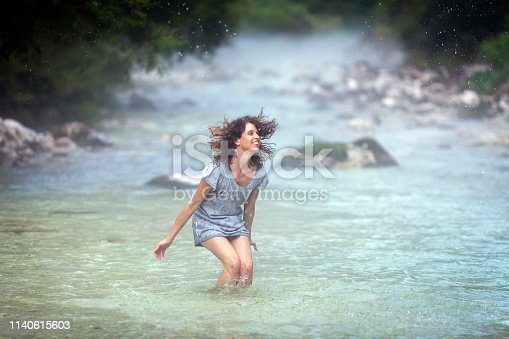Smiling Adult Woman Walking in Shallow River
