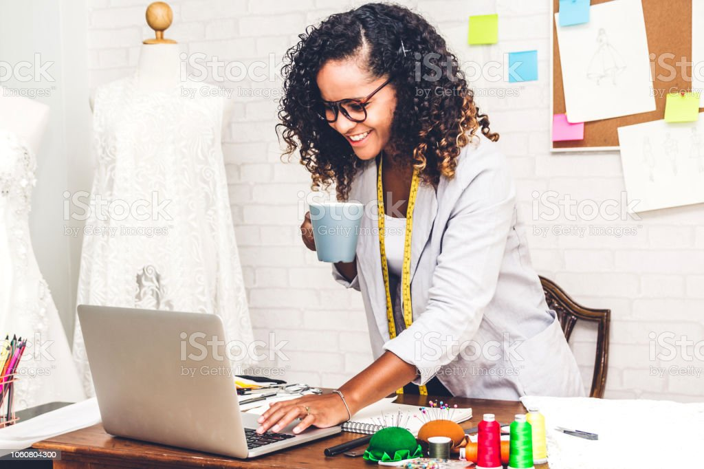 Smiling African American Black Woman Fashion Designer Standing And Working With Laptop Computer At Workshop Studio Stock Photo Download Image Now Istock