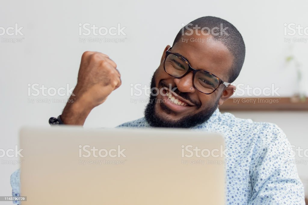 Smiling African American businessman celebrating success, using laptop - Royalty-free Achievement Stock Photo