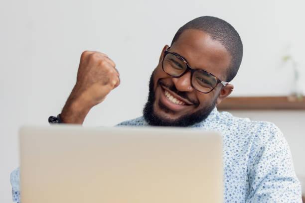 homem de negócios de sorriso do americano africano que comemora o sucesso, usando o portátil - excitação - fotografias e filmes do acervo