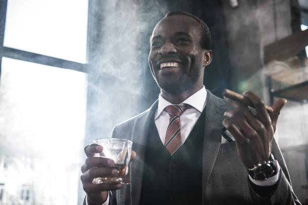 lachende afro-amerikaanse zakenman houden van glas met whisky en rookvrije sigaar - guy with cigar stockfoto's en -beelden