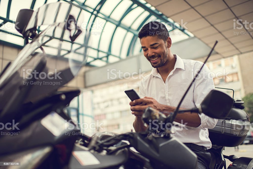 Smiling African American businessman using cell phone on motorcycle. stock photo