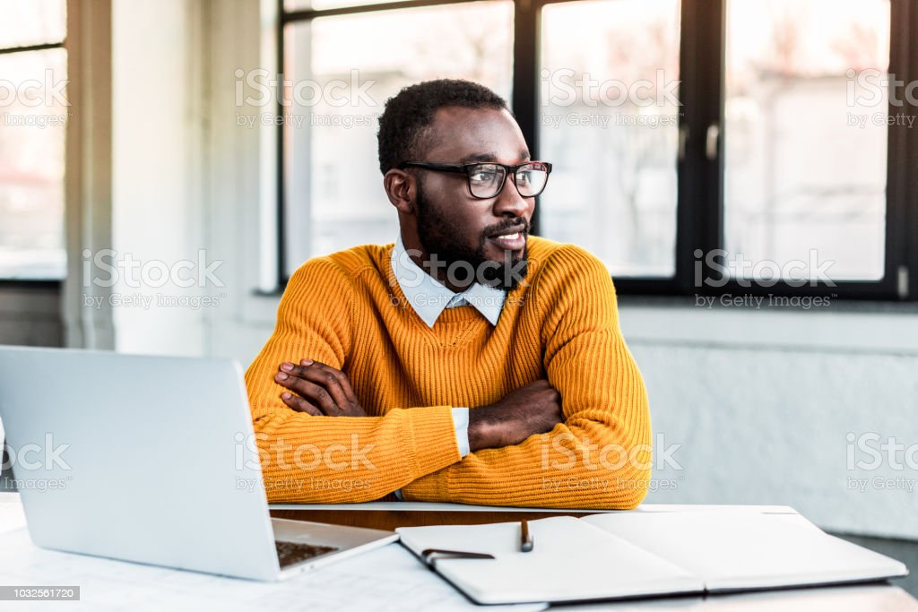 smiling african american businessman with crossed arms in office stock photo