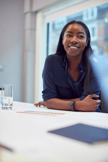 Smiling African American Businesswoman Sitting At Table In Office  Meeting Room stock photo