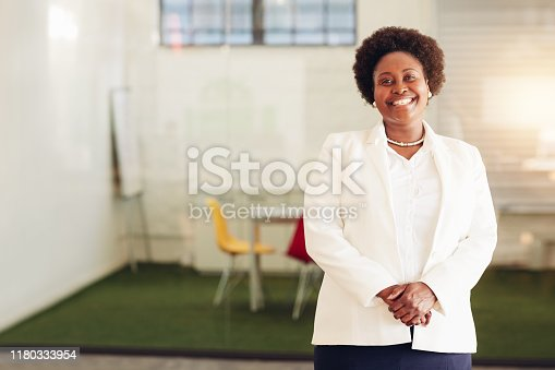 Portrait of an African American businesswoman wearing a suit and smiling while standing alone in a large modern office