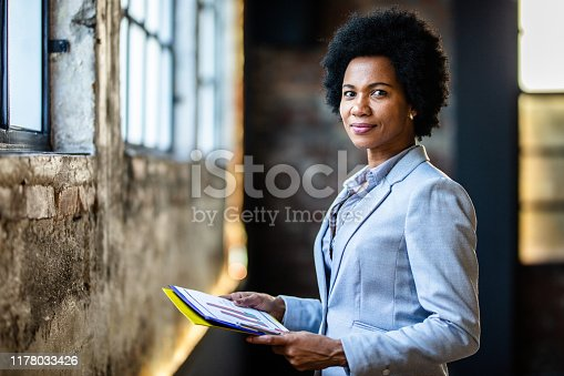 Mid adult black businesswoman analyzing reports in the office and looking at camera. Copy space.