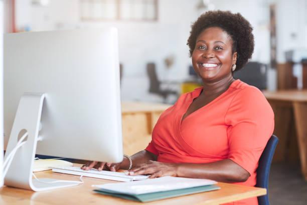 Lächelnde afroamerikanische Geschäftsfrau, die an ihrem Computer arbeitet – Foto