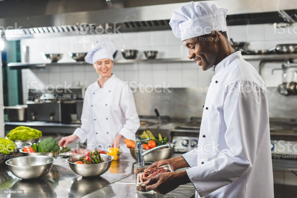 smiling african american chef holding tray with raw meat at restaurant kitchen stock photo