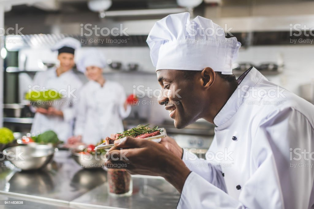smiling african american chef sniffing raw meat with herbs at restaurant kitchen stock photo