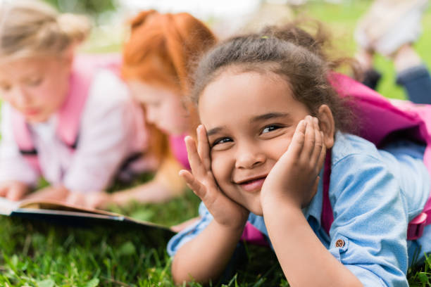 smiling african american child adorable african american girl smiling at camera while lying with friends on grass 2012 stock pictures, royalty-free photos & images