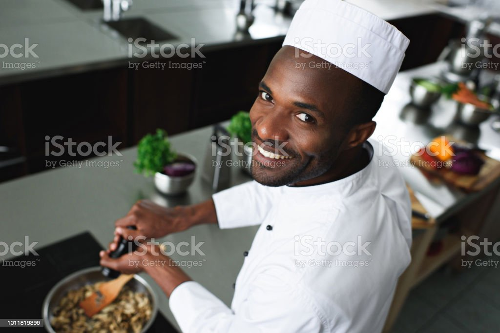 Smiling African american cook seasoning dish by kitchen stove stock photo