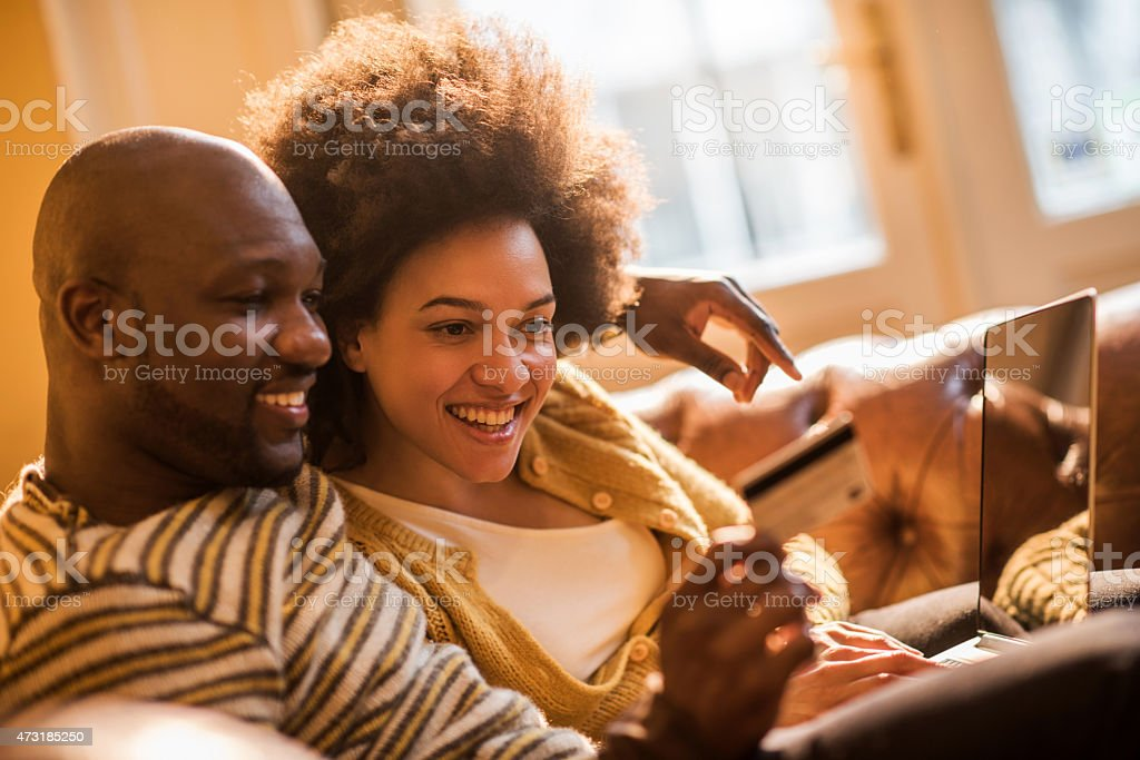 Smiling African American couple online shopping at home. stock photo