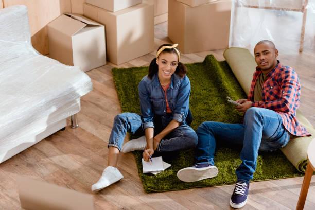 lächelnd afroamerikanischen paar budgetplanung im neuen zuhause - geld schön verpacken stock-fotos und bilder