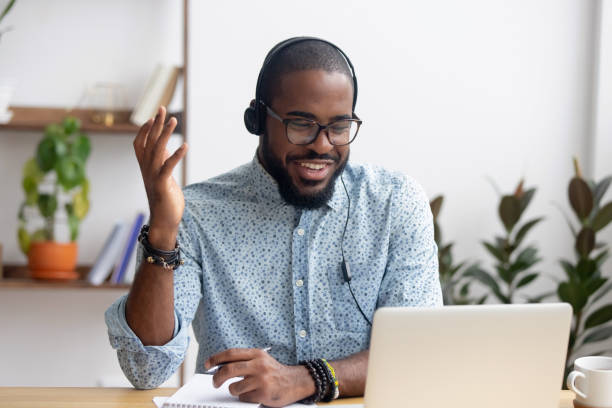 smiling african american employee in headphones using laptop - didattica a distanza foto e immagini stock