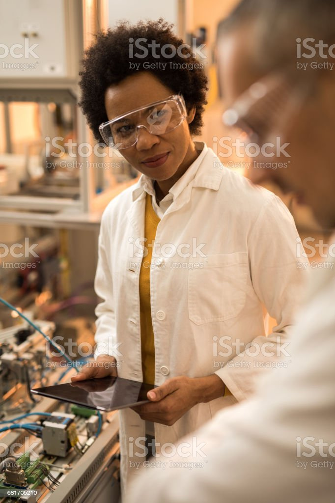 Smiling African American engineer cooperating with her colleague in laboratory. stock photo