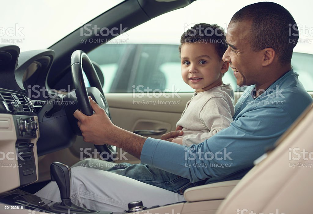 Smiling African American father and son testing car in showroom. stock photo