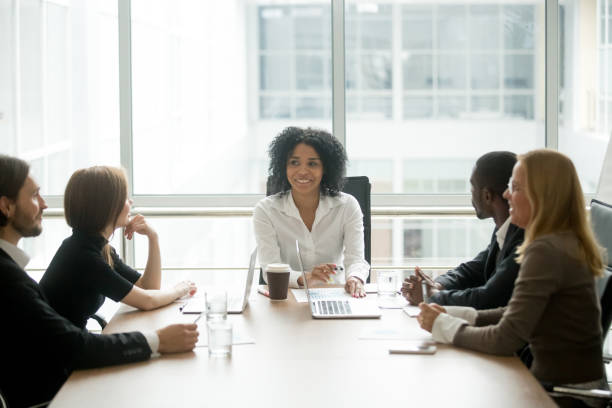 Smiling african american female boss leading corporate diverse team meeting Smiling friendly african female boss leading corporate diverse team meeting talking to multiracial partners employees discussing results or planning work at group multi-ethnic briefing in boardroom director stock pictures, royalty-free photos & images