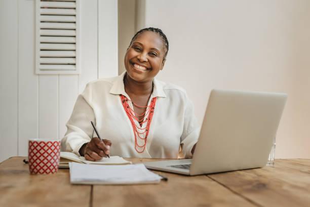 Lächelnde afroamerikanische Unternehmerin arbeitet von zu Hause aus – Foto