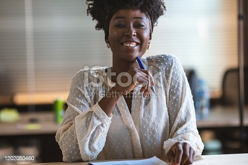 912944158istockphoto Smiling african american female freelancer working at office 1202050460