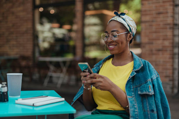 Smiling african american female with smartphone outdoors stock photo