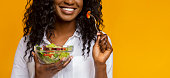 istock Smiling african american girl eating vegetable salad 1169136267