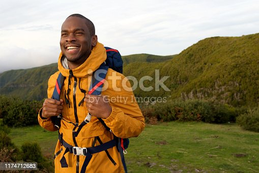 Portrait of smiling african american hiker walking with backpack in nature
