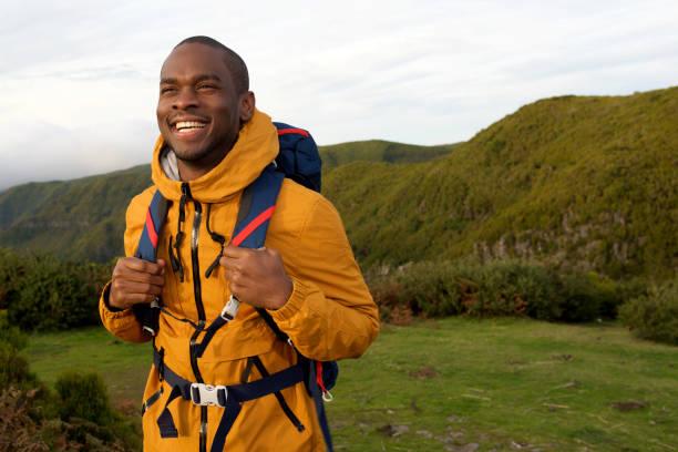lächelnde afrikanische amerikanische Wanderer zu Fuß mit Rucksack in der Natur – Foto