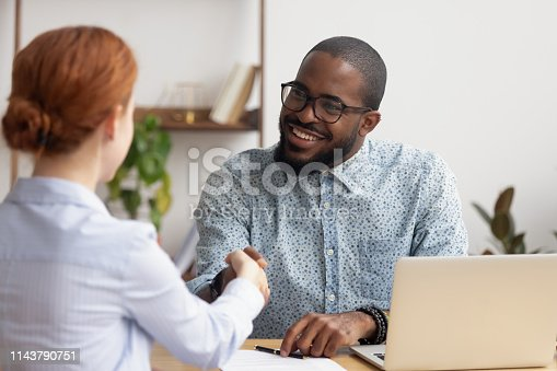 843963182 istock photo Smiling African American hr manager shaking hand of candidate 1143790751