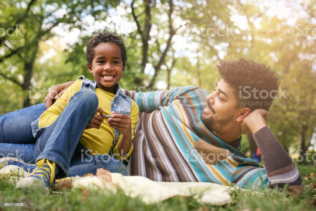 Smiling African American little girl in park with father lying down and having funny conversation. royalty-free stock photo
