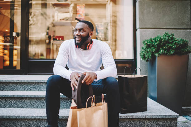Smiling african american male customer in trendy wear sitting on stairs of store with bags with copy space for label, cheerful dark skinned hipster guy recreating after shopping and buying purchases stock photo