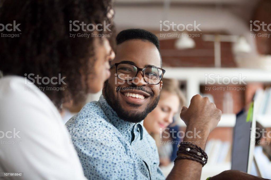 Lächelnde afrikanische amerikanische männliche Mitarbeiter Blick auf Kollegen chatten – Foto