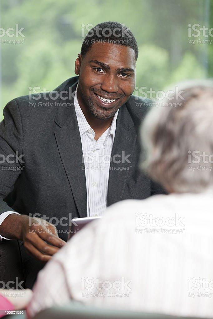 Lächelnden afroamerikanischen Mann Beratung mit einem senior Frau – Foto