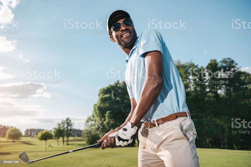 Smiling african american man in cap and sunglasses holding club and playing golf stock photo