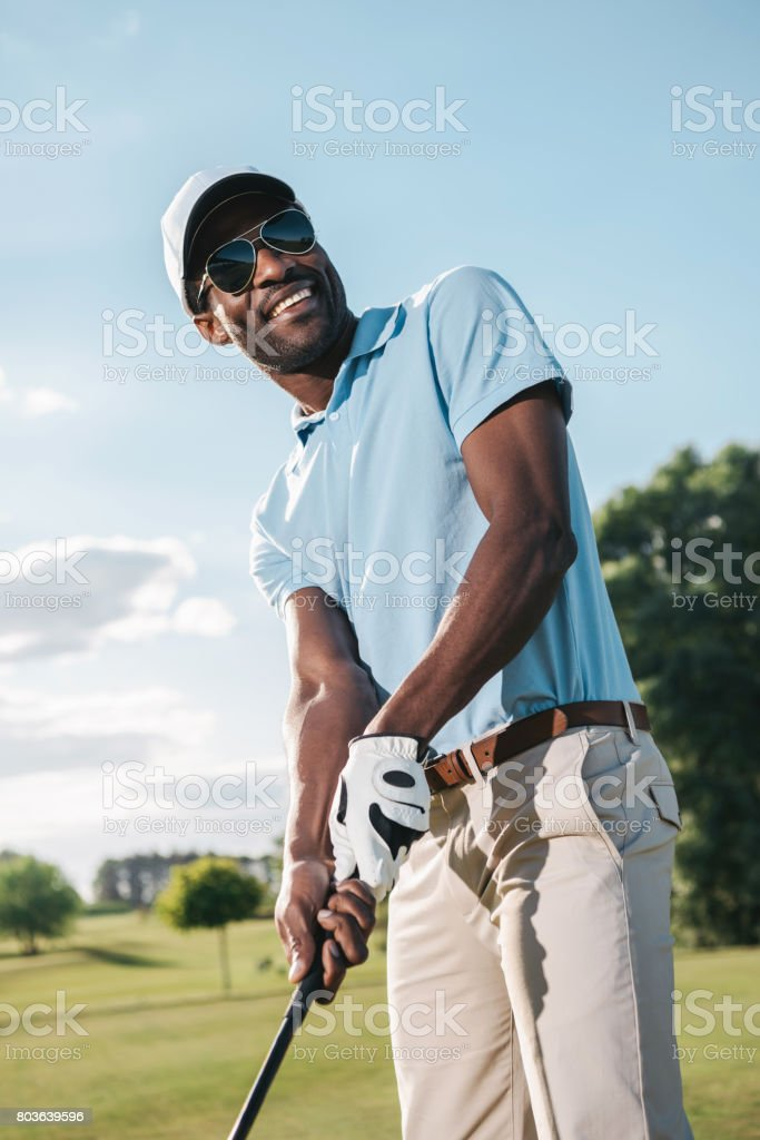 5953ce04184 Smiling african american man in cap and sunglasses holding club and playing  golf - Stock image .