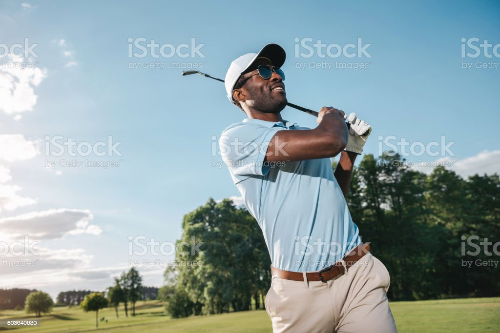 Smiling african american man in cap and sunglasses playing golf stock photo