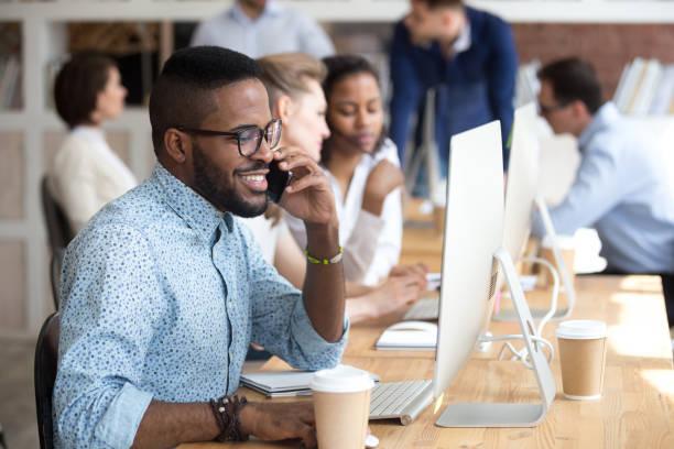 sonriente a hombre afroamericano hablando por teléfono, utilizando equipo - empleada administrativa fotografías e imágenes de stock