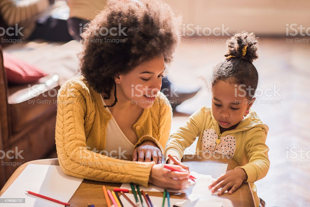 Smiling African American mother and daughter coloring together. stock photo