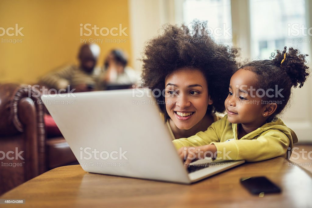 Smiling African American mother and daughter using laptop at home. stock photo